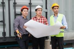 Inżynier i klient jest ubranym zbawczego hełm i projekt na ręce pracują na sprawdzać postęp budowa obraz stock