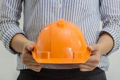 Inżynier kobiety trzymają pomarańczowego ciężkiego zbawczego hełm kapeluszowy Obraz Royalty Free