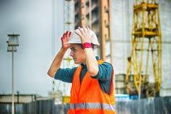 Inżynier lub architekt sprawdza osobistego ochronnego wyposażenia zbawczego hełm przy budową obraz stock