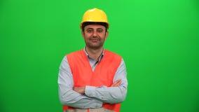 Inżynier lub pracownik budowlany patrzeje na zielonym tle zdjęcie wideo