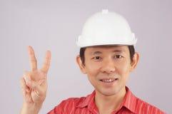 Inżynier odzieży czerwona koszula i biały kapelusz robimy sygnałowemu zwycięstwu Zdjęcia Royalty Free