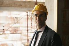 Inżynier ono uśmiecha się przy kamerą z hełmem w budowie, pora Obrazy Royalty Free