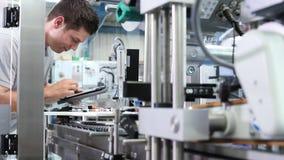 Inżynier sprawdza automatyzującą maszynę w fabryce z cyfrową pastylką zbiory