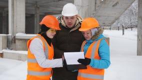 Inżynier w ciężkim kapeluszu i dwa kobieta przedstawicielach klient opowiada na śnieżystej budowie zbiory wideo