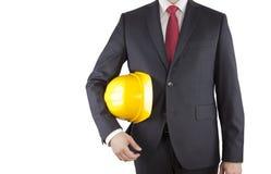 Inżynier w czarnego kostiumu mienia żółtym hełmie odizolowywającym na bielu Zdjęcia Royalty Free