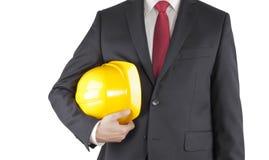 Inżynier w czarnego kostiumu mienia żółtym hełmie odizolowywającym na bielu Zdjęcie Royalty Free