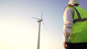 Inżynier w jaskrawej kamizelce i białego hełma pewnym kroku iść pracujący wiatraczek zbiory