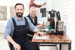 Inżynier w pracującym kombinezonie pozuje w technicznym laboratorium Za nim jest 3d drukarka zdjęcie stock