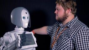 Inżynier wita białego robot i ściska zbiory