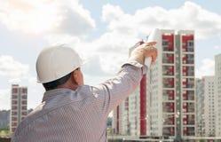 Inżynier wskazuje z projektami w jego ręce na budynkach w białym hełmie zdjęcie royalty free