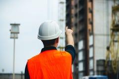 Inżynier z białym hełmem wskazuje jego rękę pokazywać budynek budowę zdjęcie royalty free