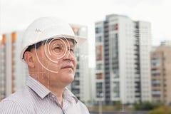 Inżynier z cyfrowym okiem technolgy na tle z budynkami obrazy royalty free
