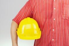 Inżynier z czerwonego koszulowego chwyta żółtym kapeluszem na białym tle Fotografia Royalty Free