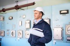 Inżynier z hełmem i projekty przy kontrolnym pokojem Zdjęcia Stock