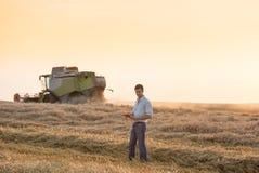 Inżynier z notatnikiem i syndykata żniwiarzem w polu Zdjęcie Royalty Free