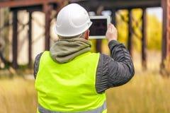 Inżynier z pastylka pecetem przy outdoors zdjęcie stock