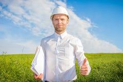 Inżyniera architekta budowniczy trzyma jego kciuk up Projektant w białych hełmów rysunkach w rękach obraz stock