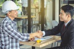 Inżyniera i biznesmena uścisku dłoni zgoda w negocjacjach wewnątrz obraz stock