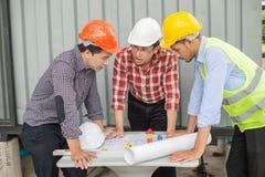 Inżyniera i budowy drużynowy patrzeje projekt i opowiada budowa proces fotografia royalty free