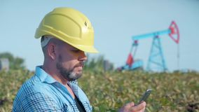 Inżyniera oilman pracy z telefonem komórkowym Nafciany świder, pole pompowa dźwigarka Pole naftowe nafciani pracownicy pracuje _ zbiory wideo