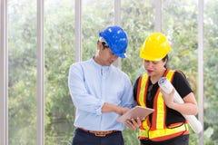 Inżyniery pracuje pokój konferencyjnego z pastylką Dwa pracownika są wa obraz royalty free
