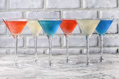 Free In Martini Glasses With A Brilliant Celebratory Drink. Red, Blue, White Alcoholic Drinks. Glitter Drink Stock Photo - 179572990