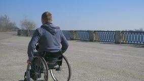 A inabilidade cansado do homem, cadeira de rodas roda, cadeira de roda de viagem da dificuldade na rua, homem deficiente na cadei vídeos de arquivo