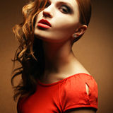 Inaccessible beautiful ginger girl in orange dress. Portrait of an inaccessible beautiful ginger girl in orange dress with smoky eyes and diamond earring. Femme Royalty Free Stock Photography