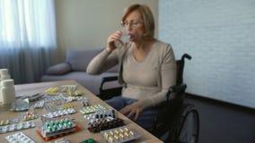Inaktivera kvinnlign i rullstol som dricker preventivpillerar med vatten, återställningen, vårdhem arkivfilmer