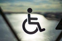 Inaktivera rullstolen för att underteckna offentligt trans. på dörrexponeringsglas med bakgrunden av solreflexionen i havsolnedgå royaltyfri foto