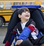 Inaktiverad pojke i rullstol, med bussen Fotografering för Bildbyråer