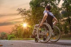 Inaktiverade eller handikapp den unga mannen på rullstolen i natur på solnedgången royaltyfria foton