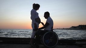 Inaktiverade lyssnar magen av hans fru i afton, ogiltig make i rullstol med den gravida kvinnlign på solnedgången arkivfilmer