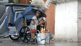 Inaktiverade på rullstolen, och den blinda mannen tigger under regn arkivfilmer