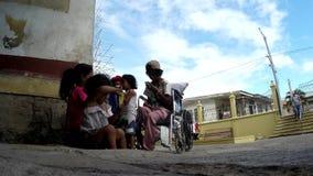 Inaktiverade tiggaren, kvinnan och barn som sitter på den kyrkliga portalen arkivfilmer