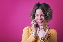 Inappropriate casual phone call. Cute goofy girl having an embarrassing phone call, gossips with her friend over her cell phone, vivid pink background royalty free stock photography
