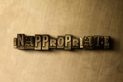 INAPPROPRIATE - close-up of grungy vintage typeset word on metal backdrop Stock Photos