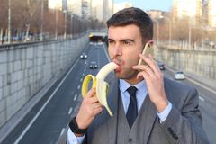Inappropriate man biting a banana while calling stock photography