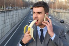 Inappropriate man biting a banana while calling.  stock photos