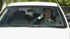 Inattentive automobilist talking on phone suddenly pressing breaks, road safety. Stock footage stock footage