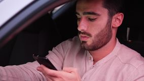 Young Man Using his Cell Phone Driving a Car stock video footage