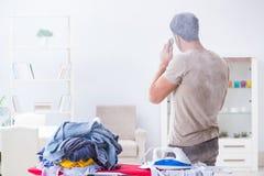 The inattentive husband burning clothing while ironing. Inattentive husband burning clothing while ironing Royalty Free Stock Image