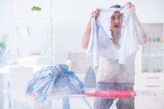 The inattentive husband burning clothing while ironing. Inattentive husband burning clothing while ironing Stock Image
