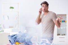 The inattentive husband burning clothing while ironing. Inattentive husband burning clothing while ironing Royalty Free Stock Images