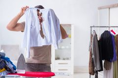 The inattentive husband burning clothing while ironing. Inattentive husband burning clothing while ironing Royalty Free Stock Photo