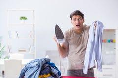 The inattentive husband burning clothing while ironing. Inattentive husband burning clothing while ironing Stock Photo
