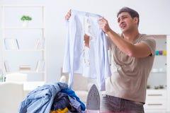 The inattentive husband burning clothing while ironing. Inattentive husband burning clothing while ironing Stock Photos
