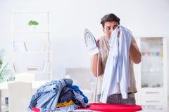 The inattentive husband burning clothing while ironing. Inattentive husband burning clothing while ironing Royalty Free Stock Photos