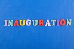 inauguración Palabra inglesa en el fondo azul compuesto de letras de madera del ABC del bloque colorido del alfabeto, espacio de  Foto de archivo