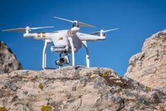 Inbillat quadcoptersurr på en klippa Arkivbilder